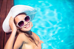 Beautiful woman wearing sunglasses and straw hat leaning on wooden deck by poolside Stock Image
