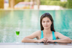 Beautiful woman wearing swimming wear. Looking to camera at border of swimming pool Stock Photo