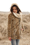 Beautiful woman wearing tigerprint coat in snow. Beautiful young woman wearing a tigerprint coat and white scarf in the snow Stock Photos