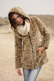 Beautiful woman wearing tigerprint coat in snow. Beautiful young woman wearing a tigerprint coat and white scarf in the snow Royalty Free Stock Photo