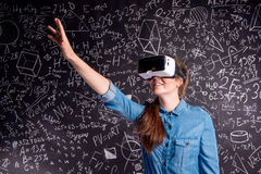 Beautiful woman wearing virtual reality goggles against big blac Stock Images