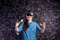 Beautiful woman wearing virtual reality goggles against big blac Stock Photo