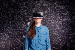 Beautiful woman wearing virtual reality goggles against big blac Royalty Free Stock Photography