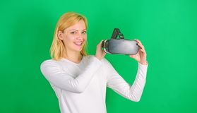 Beautiful woman wearing virtual reality goggles in studio. Person with virtual reality helmet  on green. Background. Amazed young woman touching the air during stock images