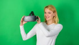Beautiful woman wearing virtual reality goggles in studio. Person with virtual reality helmet isolated on green. Background. Amazed young woman touching the air stock image