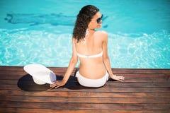 Beautiful woman wearing white bikini and hat sitting near pool Royalty Free Stock Images