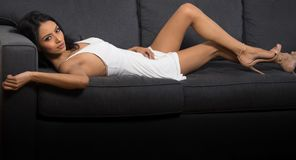 Beautiful woman wearing white dress lying on couch Royalty Free Stock Images