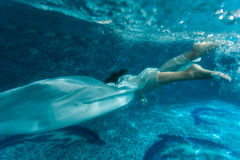 Beautiful woman wearing white fabric diving in pool Stock Images