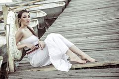 Beautiful woman wearing white summer dress sitting on wooden pie. R Stock Photography