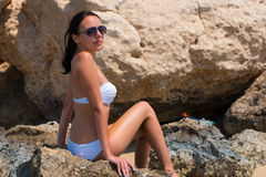 Beautiful woman wearing white swimsuit and sunglasses sitting on Royalty Free Stock Images