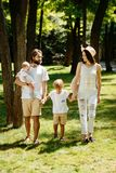 Beautiful woman wears the white clothes and hat walks with handsome father and children in the wonderful park on a stock photography
