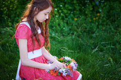 Beautiful woman weaves a wreath on the grass Stock Photos