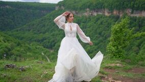 A beautiful woman in a wedding dress and black boots posing in the mountains.