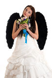 Beautiful woman in a wedding dress with black wings Stock Photo