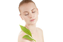 Beautiful woman with a  well-groomed complexion. Beautiful woman with a healthy and well-groomed complexion holding green leaf . Spy beauty skin treatment woman Stock Photo