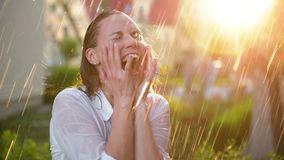 Beautiful Woman With Wet Hair Enjoying the Rain And Looking Up To the Sky. Pretty Woman in Summer Garden Having a lot of. Fun. Happy Rainy Day. Colorful Video stock footage