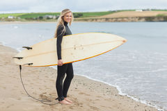 Beautiful woman in wet suit holding surfboard at beach Stock Images