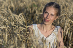 Beautiful woman in wheat at sunset. Stock Photo