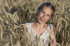 Beautiful woman in wheat at sunset. Royalty Free Stock Photo