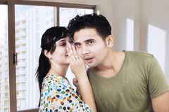Beautiful woman whispering to boyfriend's ear. Asian girl spreads the good news to her boyfriend Stock Images