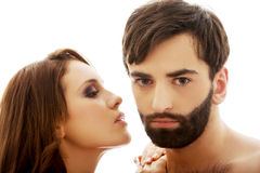 Beautiful woman whispering to man's ear. Royalty Free Stock Image