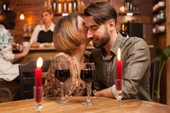 Beautiful woman whispers to her handsome boyfriend ear how much she loves him stock image