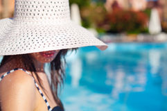 Beautiful woman in white big hat near pool on a sunny day Royalty Free Stock Photography