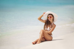 Beautiful woman in a white bikini and hat on the beach. Stock Photography