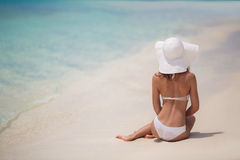 Beautiful woman in a white bikini and hat on the beach. Stock Photos