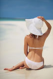 Beautiful woman in a white bikini and hat on the beach. Stock Photo