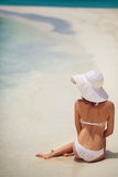 Beautiful woman in a white bikini and hat on the beach. Royalty Free Stock Photo