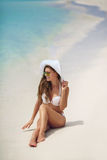 Beautiful woman in a white bikini and hat on the beach. Royalty Free Stock Image