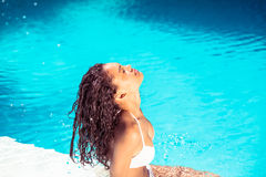 Beautiful woman in white bikini sitting by pool side Royalty Free Stock Photography