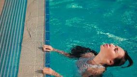 Beautiful woman in white bikini swimming in the blue pool stock video