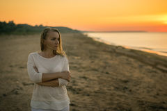Beautiful woman in white clothes enjoying the sunset on the beach. royalty free stock photos
