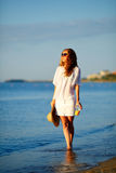 Beautiful woman in white clothes with orange juice, sunglasses and hat in hand on the beach Royalty Free Stock Photography
