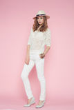 Beautiful woman in white clothes posing on pink background in hat Stock Photo