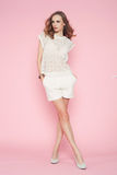 Beautiful woman in white clothes posing on pink background Stock Photo