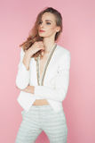 Beautiful woman in white clothes posing on pink background Royalty Free Stock Image