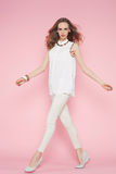 Beautiful woman in white clothes posing on pink background Royalty Free Stock Photo