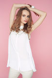 Beautiful woman in white clothes posing on pink background Stock Photos
