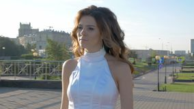 A beautiful woman in white clothes is walking along the street. stock video