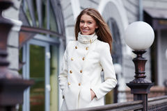 Beautiful woman in white coat on the city street Stock Image