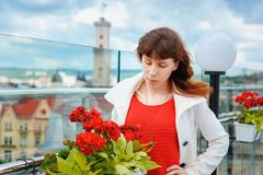 Beautiful woman in a white coat near the red flowers in the background Lviv Stock Images