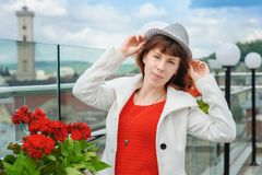 Beautiful woman in a white coat near the red flowers in the background Lviv.  Stock Images