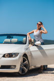 Beautiful woman in a white convertible car. Portrait of a beautiful young woman,brunette with a long braid,wearing dark glasses,a striped t-shirt,posing alone royalty free stock image