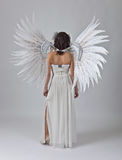 Beautiful woman in white dress with angel wings. Young beautiful woman in white dress with angel wings Stock Images