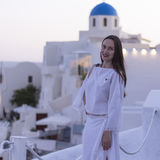 Beautiful woman in white dress on background of the architecture in Santorini. sunset Royalty Free Stock Photo