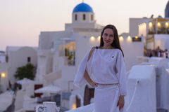 Beautiful woman in white dress on background of the architecture in Santorini. sunset Stock Photo