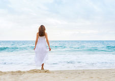 Beautiful woman in a white dress on the beach Stock Photo